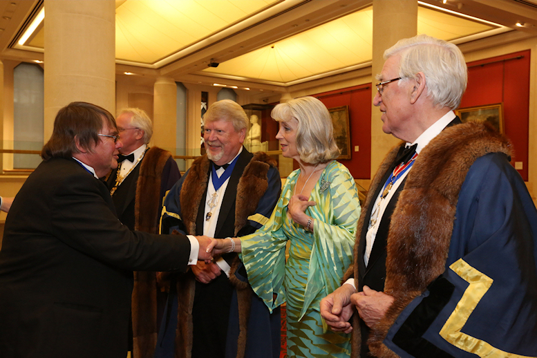 As Senior Warden, John welcomes guests to the Midsummer Banquet of the Musicians' Company, The Guildhall, June 2012  <br> (l-r: Michael Spencer, Alderman Sir Andrew Parmley (Master, partly hidden), John and Marie, Sir Anthony Cleaver (Junior Warden)
